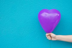 Young Caucasian Woman Girl Holds in Hand Purple Heart Shaped Air Balloon on Turquoise Painted Wall Background. Love Charity. Donation Kids Romantic Concept royalty free stock photos