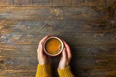 Young caucasian woman girl in knitted yellow sweater holds in hands mug with freshly brewed coffee with appetizing crema on table. Young caucasian woman girl in stock photos