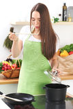 Young caucasian woman in a green apron cooking in the kitchen. Housewife is tasting soup by wooden spoon. Food and Stock Photography