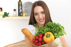 Young caucasian woman in a green apron is holding paper bag full of vegetables and fruits while smiling in kitchen Stock Photography