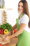 Young caucasian woman in a green apron is holding paper bag full of vegetables and fruits while smiling in kitchen Royalty Free Stock Photography