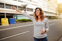 Young caucasian woman hailing a cab. Side view of a young caucasian woman hailing a cab while holding a smart phone Stock Photography