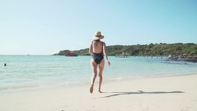 Young caucasian woman happily runs into sea water. Girl in a bathing suit and a straw hat enjoys vacation on paradise tropical island with sandy beach and calm stock video