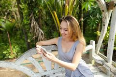 Young caucasian woman hatting by smartphone with palms in background, sitting on swing. royalty free stock image
