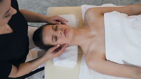 Young caucasian woman having treatment massage on the face in the massage salon. stock video footage