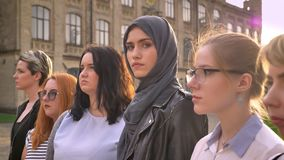Young caucasian woman in hijab directly among of other diverse girls in line outside stock footage