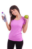 Young caucasian woman holding a bottle of water and an apple Stock Image