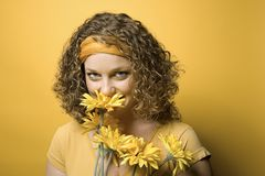 Young Caucasian woman holding flowers. Portrait of young adult Caucasian woman on yellow background holding and smelling bouquet of flowers Stock Photo