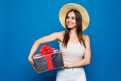 Young caucasian woman holding a gift box, smiling and looking at camera on blue background. Young caucasian woman holding a gift box, smiling and looking at Royalty Free Stock Image