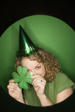 Young Caucasian woman holding shamrock. Vignette of young adult Caucasian woman on green background wearing Saint Patricks Day hat and holding shamrock Stock Photos