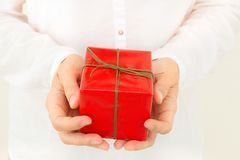 Young caucasian woman holds in hands gift box wrapped in red paper tied with green ribbon. Pastel colors. Christmas. Young caucasian woman holds in hands gift stock photo