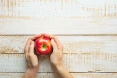 Young Caucasian Woman Holds in Hands Ripe Red Apple on White Plank Wood Background Tabletop. Flat Lay Top View Thanksgiving royalty free stock photo