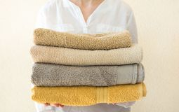 Young caucasian woman holds in hands stack of clean folded terry towels. White wall background. Laundry spa wellness cleanliness. Concept. Provence royalty free stock photo