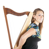 Young caucasian woman holds small harp in studio against white b Royalty Free Stock Photo