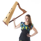 Young caucasian woman holds up small harp in studio against whit Royalty Free Stock Images