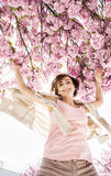 Young caucasian woman is jumping under the flowering sakura tree Royalty Free Stock Photos