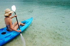 Young caucasian woman kayaking over turquoise water Stock Photography