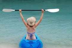 Young caucasian woman kayaking over turquoise water Royalty Free Stock Images