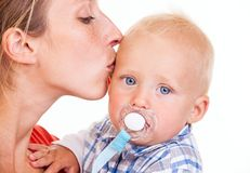 Young Caucasian woman kissing her baby son. Young Caucasian women kissing her baby son over white, closeup view Stock Image