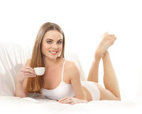 A young Caucasian woman laying in white lingerie Royalty Free Stock Photo