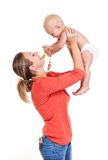 Young Caucasian woman lifting her baby son. Young Caucasian women lifting her baby son over white, boy playing with nursing necklace Royalty Free Stock Photography