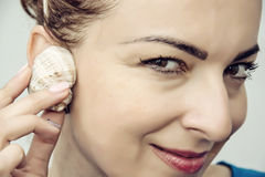Young caucasian woman listening the seashell, closeup portrait royalty free stock photos