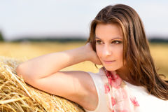 Young Caucasian woman with long brown hair leaning against a bale of straw Stock Photos
