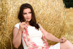 Young Caucasian woman with long brown hair leaning against a bale of straw Royalty Free Stock Images