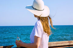 Young caucasian woman with long hair in sunhat and white shirt standing at the seafront, looking at horizon. Blue aquamarine water, holding bottle with juice Stock Photo