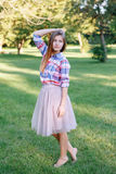 Young Caucasian woman with long red hair in plaid shirt posing in park Royalty Free Stock Photo