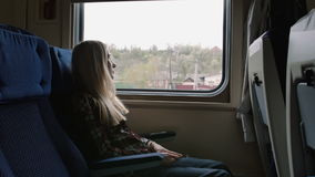 Young caucasian Woman look thru the window while traveling by train. Young girl look thru the window while traveling by train stock footage
