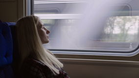 Young caucasian Woman look thru the window while traveling by train. Young girl look thru the window while traveling by train stock video footage