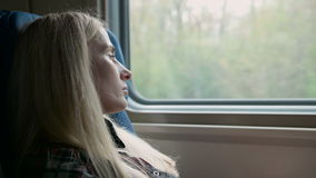 Young caucasian Woman look thru the window while traveling by train. Young girl look thru the window while traveling by train stock video