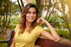 Young caucasian woman looking away with confidence. Young caucasian woman in yellow shirt looking away with confidence while sitting outdoors stock image