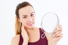 Young caucasian woman looking wrinkles on face in mirror isolated on white background. Skin care, anti aging and makeup concept. royalty free stock photography