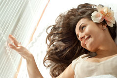 Young Caucasian woman lying in bed with flowers Royalty Free Stock Photography
