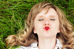 Young caucasian woman lying down on green grass with eyes closed. Holding on her lips a small red sweet heart-shaped candy like sh Royalty Free Stock Photography
