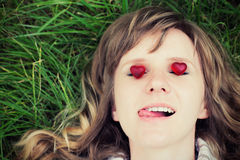 Young caucasian woman is lying down on green grass with eyes closed and sticking out tongue. There are two small red sweet. Heart-shaped candies on her eyes royalty free stock photo