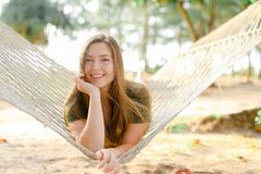 Young caucasian woman lying on white wicker hammock and wearing khaki dress. royalty free stock photos