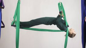 Young caucasian woman making antigravity fly yoga exercises in hammock in studio indoors. Aerial aero fly fitness. Trainer workout. Layback pose, meditates stock video footage