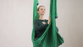 Young caucasian woman making antigravity fly yoga exercises in hammock in studio indoors. Aerial aero fly fitness. Trainer workout. Lotus pose, meditates stock video