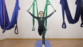 Young caucasian woman making antigravity fly yoga exercises in hammock in studio indoors. Aerial aero fly fitness. Trainer workout. Twine, split, meditates stock video