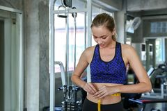 Young caucasian woman measuring waist in gym. Slim woman measuring her thin waist with a tape measure. smiling people with measure stock images