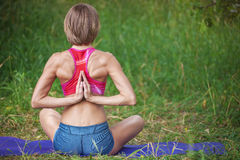 Young Caucasian woman meditating in lotus position. Stock Photos