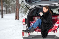 Young Caucasian woman in mink fur sitting in car trunk and drinking hot tea. Walking in winter forests Stock Photography