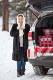 Young Caucasian woman in mink fur standing full-length near own car and drinking hot tea. Walking in winter forest Stock Photography