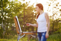 Young caucasian woman painting outdoors Stock Photography
