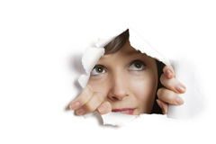 Young Caucasian woman peeking from ripped paper hole Royalty Free Stock Image