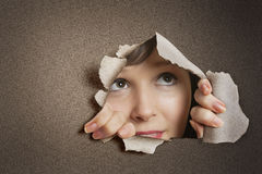 Young Caucasian woman peeking from ripped paper hole Stock Image