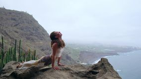 Young Caucasian woman performing upward facing dog pose outdoorsThe woman sitting on the edge of a cliff in the pose of